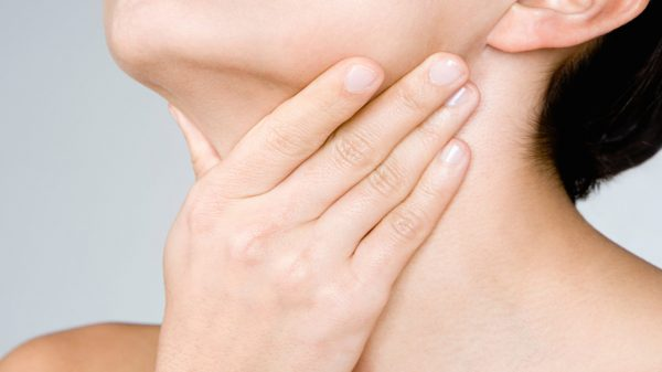 Lady holding her hand against her neck in pain